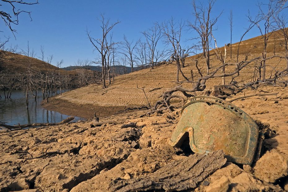 A mask lays on the ground covered in dirt on the dried out remains of a lake below Tuttletown Campground at New Melones Lake, California..