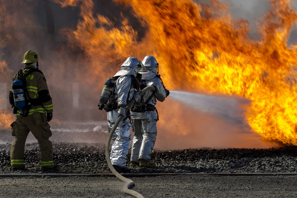 Two firefighters extinguish a burning aircraft.