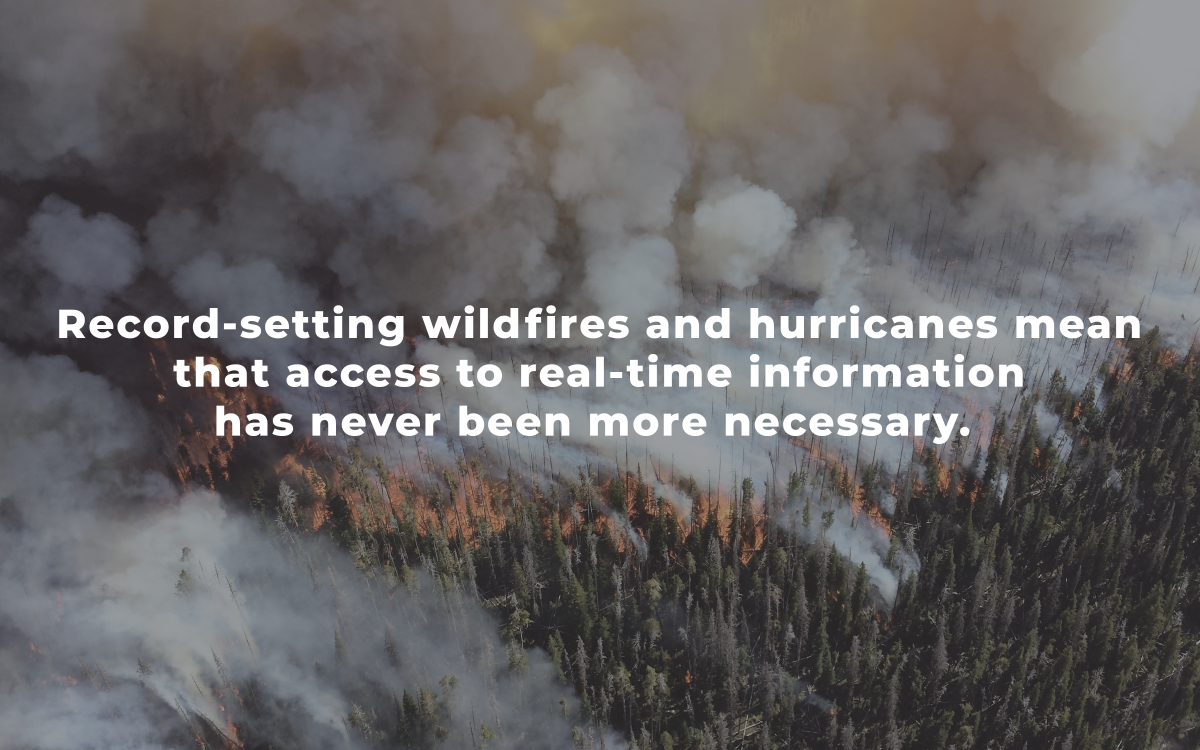 """A photo of a wildfire, with text overlayed that reads """"Record-setting wildfires and hurricanes mean that access to real-time information has never been more necessary."""""""