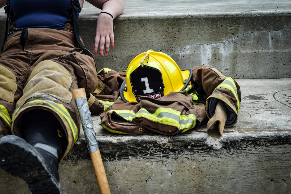 A firefighter sits on the ground next to their equipment.